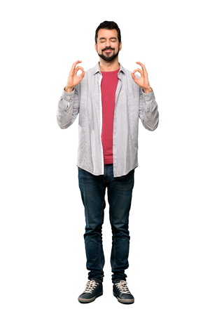 Full-length shot of Handsome man with beard in zen pose over isolated white background