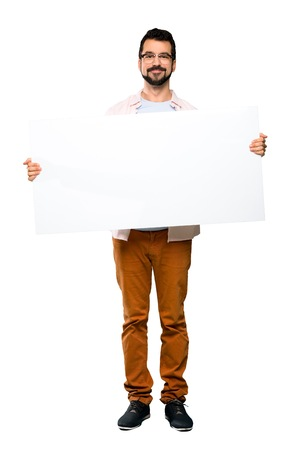 Full-length shot of Handsome man with beard holding an empty placard over isolated white background