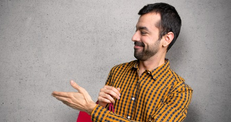 Man with shopping bags handshaking after good deal over textured wall