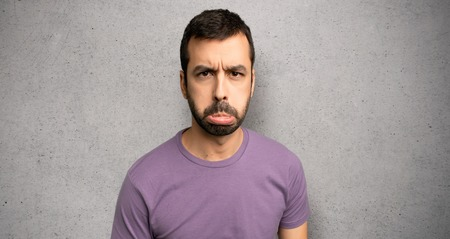 Handsome man with sad and depressed expression over textured wall Stock Photo