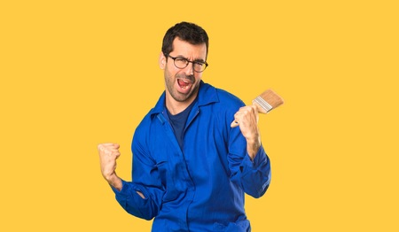 Painter man celebrating a victory on isolated yellow background
