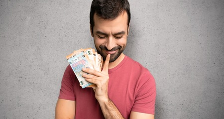 Man taking a lot of money looking down with the hand on the chin over textured wall Stock Photo