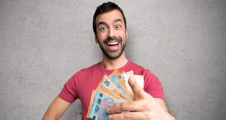 Man taking a lot of money points finger at you with a confident expression over textured wall Stockfoto
