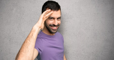 Handsome man saluting with hand over textured wall Stock Photo