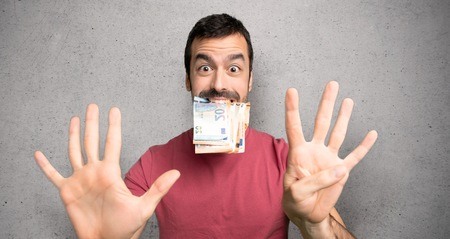 Man taking a lot of money counting nine with fingers over textured wall