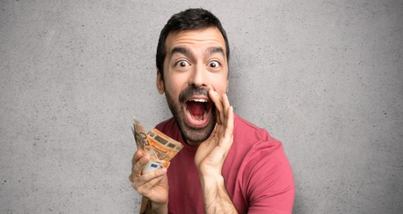 Man taking a lot of money shouting and announcing something over textured wall