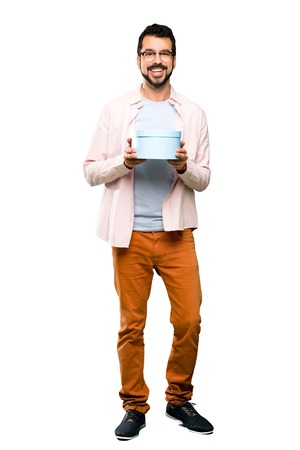Full-length shot of Handsome man with beard holding a gift over isolated white background