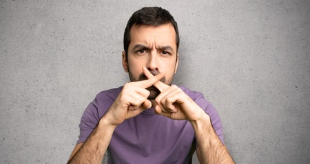 Handsome man showing a sign of silence gesture over textured wall Stock Photo