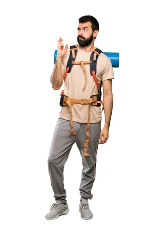 Hiker man with fingers crossing and wishing the best over isolated white background