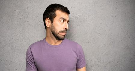 Der gutaussehende Mann ist ein bisschen nervös und hat Angst, die Zähne über eine strukturierte Wand zu drücken