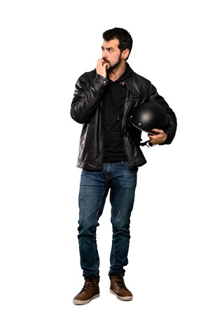 Full-length shot of Biker man nervous and scared putting hands to mouth over isolated white background Banco de Imagens
