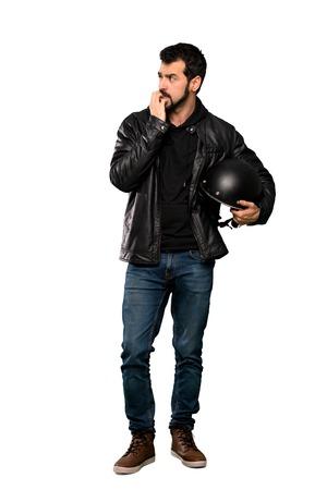 Plan complet d'un homme de motard nerveux et effrayé mettant les mains à la bouche sur fond blanc isolé Banque d'images