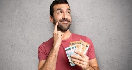 Man taking a lot of money thinking an idea while looking up over textured wall