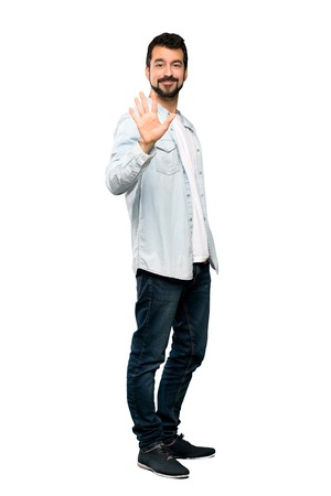 Full-length shot of Handsome man with beard counting five with fingers over isolated white background Stock Photo