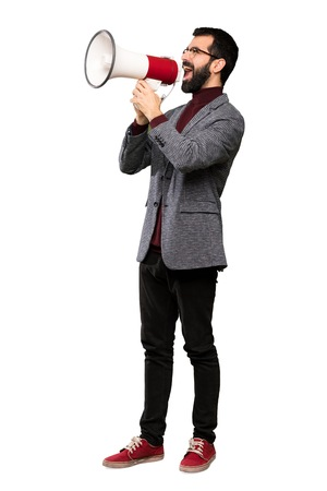 Handsome man with glasses shouting through a megaphone over isolated white background