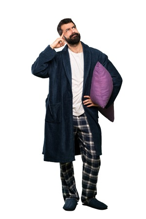 Man with beard in pajamas having doubts and thinking over isolated white background Imagens