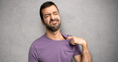 Handsome man with tired and sick expression over textured wall Stock Photo