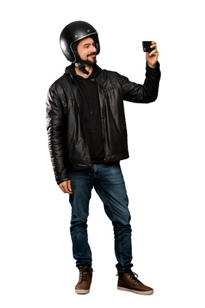 Full-length shot of Biker man making a selfie over isolated white background