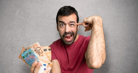 Man taking a lot of money making the gesture of madness putting finger on the head over textured wall Stock Photo