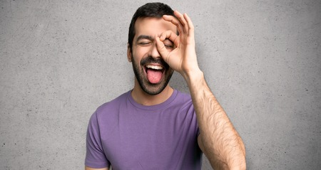 Handsome man makes funny and crazy face emotion over textured wall