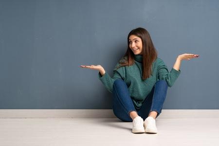 Giovane donna seduta sul pavimento tenendo copyspace con due mani