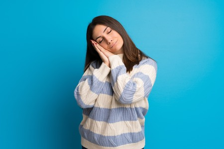 Young woman over blue wall making sleep gesture in dorable expression Stock Photo
