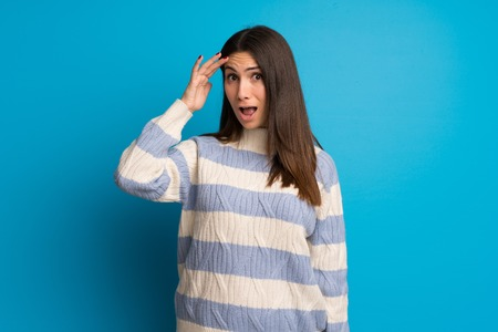 Young woman over blue wall has just realized something and has intending the solution
