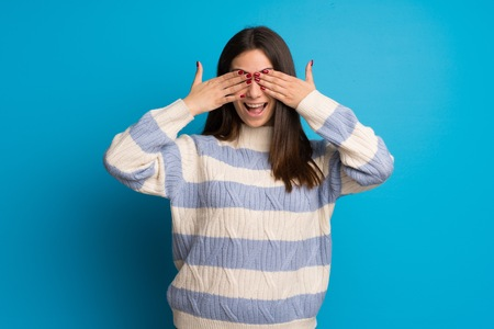 Young woman over blue wall covering eyes by hands. Surprised to see what is ahead
