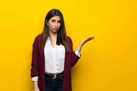 Young woman over yellow wall making doubts gesture