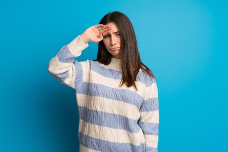 Young woman over blue wall with tired and sick expression