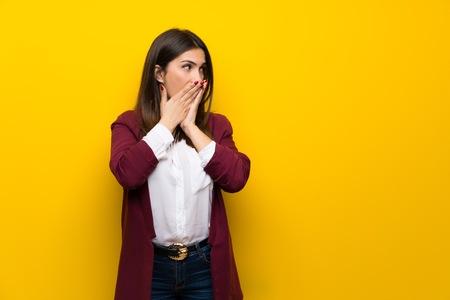 Jonge vrouw over gele muur die mond bedekt en naar de zijkant kijkt