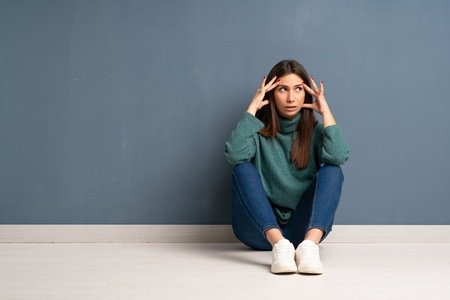 Young woman sitting on the floor with headache