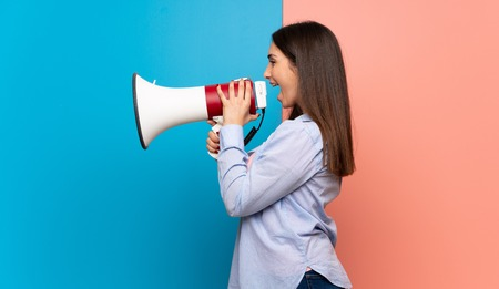 Young woman over pink and blue wall shouting through a megaphone