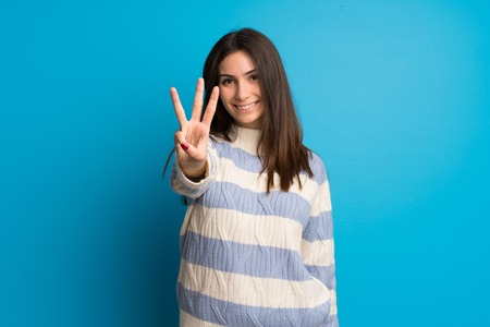 Young woman over blue wall happy and counting three with fingers