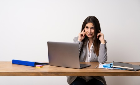 Business woman in a office frustrated and covering ears with hands