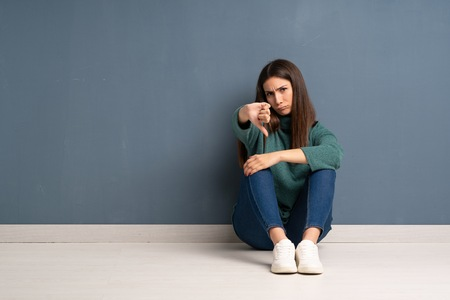 Young woman sitting on the floor showing thumb down with negative expression