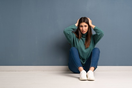 Young woman sitting on the floor frustrated and takes hands on head
