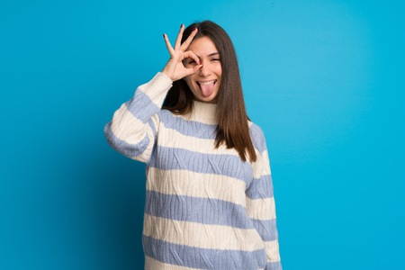 Young woman over blue wall makes funny and crazy face emotion