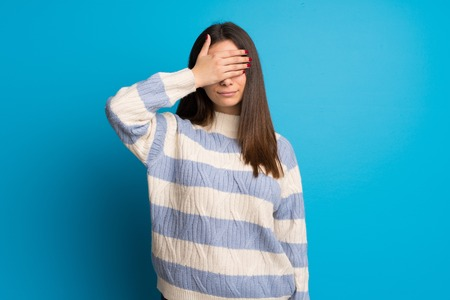 Young woman over blue wall covering eyes by hands. Do not want to see something Imagens