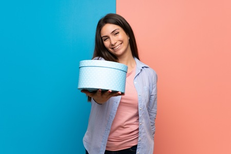 Young woman over pink and blue wall holding a gift in hands Stock Photo