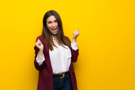 Young woman over yellow wall celebrating a victory in winner position