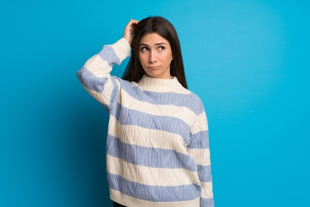 Young woman over blue wall having doubts while scratching head Imagens