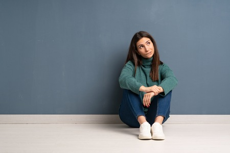 Young woman sitting on the floor with confuse face expression while bites lip