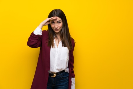 Young woman over yellow wall looking far away with hand to look something