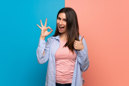Young woman over pink and blue wall showing ok sign with and giving a thumb up gesture Фото со стока
