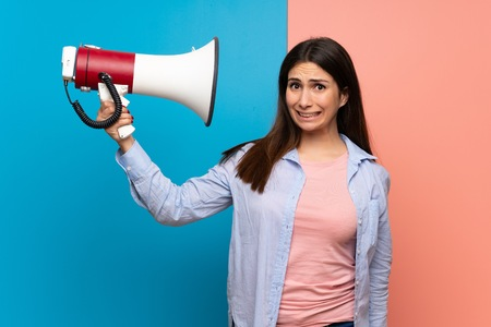 Young woman over pink and blue wall taking a megaphone that makes a lot of noise