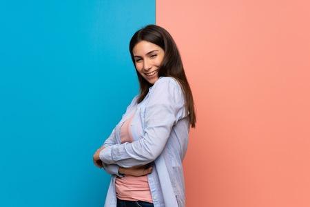 Jonge vrouw over roze en blauwe muur lachend
