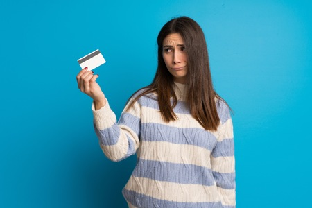 Young woman over blue wall taking a credit card without money