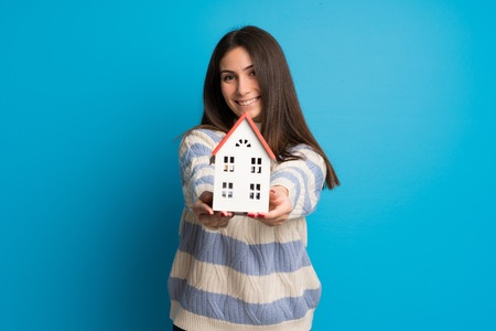 Young woman over blue wall holding a little house Banco de Imagens