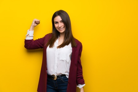 Young woman over yellow wall Doing strong gesture